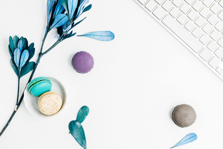 Top view flat lay colorful macarons with keyboard and blue leaves. Creative dessert concept