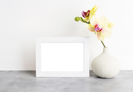 Bright photoframe mockup with yellow orchid against white wall. Interior design concept. Text space