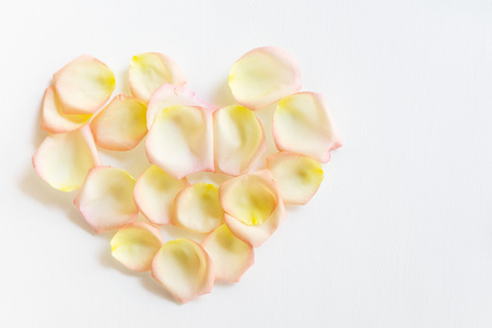 Top view flat lay Yellow and pink tea rose petals in heart shape on white background. Love, romance, valentines day concept. Text space
