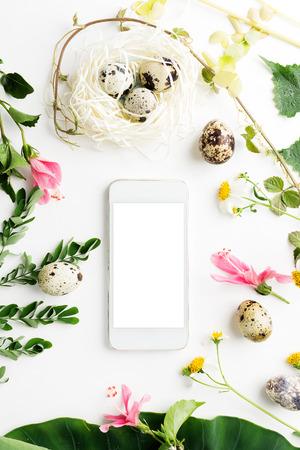 Draufsicht flach gelegt Ostermodell: weißes Handy mit Wachteleiern, Blättern und Gänseblümchen. Urlaubskonzept. Textraum