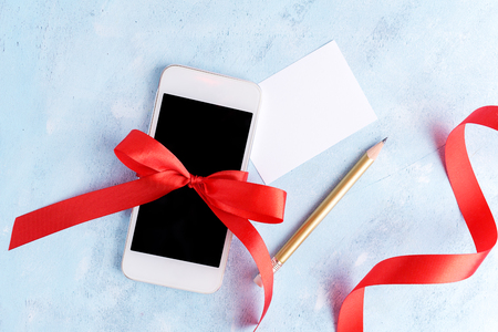 Flat lay, top view mobile phone with red bow with empty card, pencil and red ribbon  on blue background. Christmas gift, holiday concept. Text space. Lettering blank
