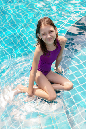 Cute smiling preteen girl sitting at swimming pool edge. Travel, vacation, childhood concept