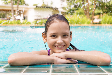 Cute smiling preteen girl at swimming pool edge. Travel, vacation, childhood concept