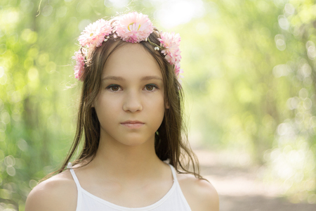 Beautiful caucasian preteen girl wearing flower wreath and white dress in forest. Fairy background. Boho style portrait. Text space