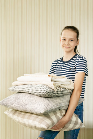 smiling preteen girl holding stack of pillows and blankets. Homework, home textile concept 版權商用圖片