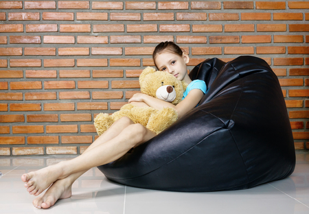 beautiful caucasian teen girl sitting in black bean bag chair against brick wall. Casual outfit. Childhood concept