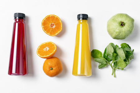 Fresh fruits in raws with juice bottles on white background. Red, orange, yellow and green. Food ingredients, Standard-Bild