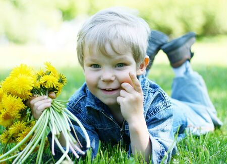 Funny kid with dandelions on green grass Stock Photo - 4565735