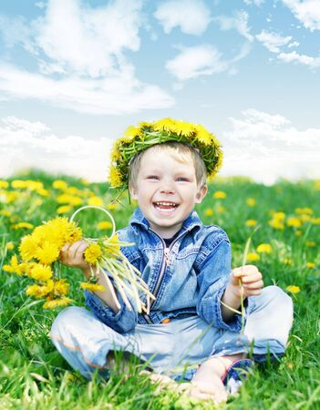 Happy kid with diadem and dandelions on green grass