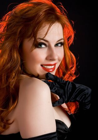 Smiling sexy woman with red hair and black gloves photo