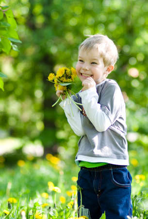 Happy kid with dandelions on summer park