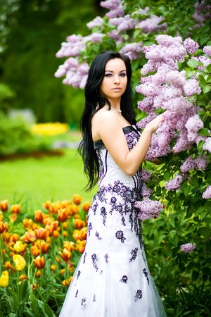 Beautiful young woman in blooming garden Stock Photo