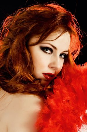 Beautiful redhead woman with red fan photo