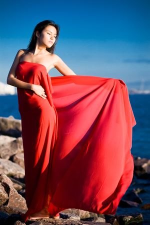 blissful: Beautiful asian girl with red dress and scarf on seashore