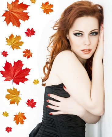 Beautyful redhead woman with autumn leaves photo