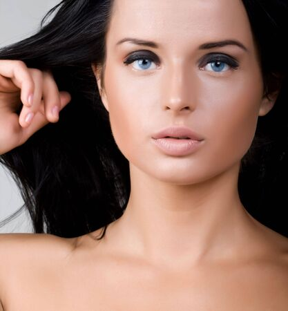 Closeup portrait of beautiful young woman with long black hair and blue eyes photo