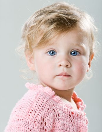 Portrait of beautiful little girl with big blue eyes closeup