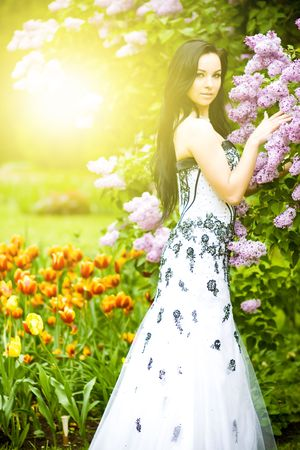 Beautiful young woman in blooming sunny garden