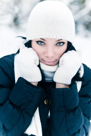 Portrait of beautiful young woman in winter park photo