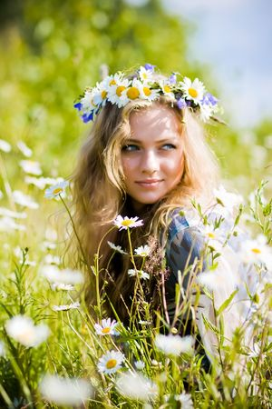 Beautiful young girl with diadem on camomile field