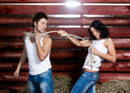 domination: Young woman catching a man with rope Stock Photo