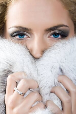 Closeup face of beautiful young woman with blue fox fur photo