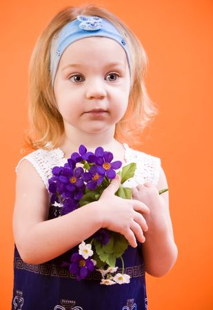 Portrait of touching little gir with flowers photo