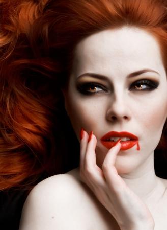 imp: Closeup portrait of beautiful redhead vampire woman Stock Photo