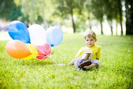 Funny little boy with colorful balloons in summer park
