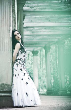 tuinhuis: Mooie jonge vrouw in witte jurk in verleden Stockfoto