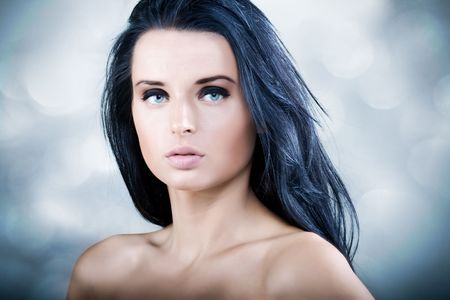 Beautiful young woman with long black hair and blue eyes photo