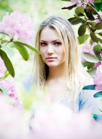 Beautiful young woman in blooming garden photo