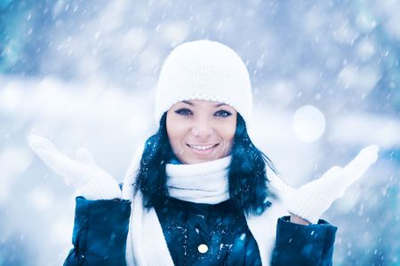 Winter portrait of beautiful smiling woman with snowflakes
