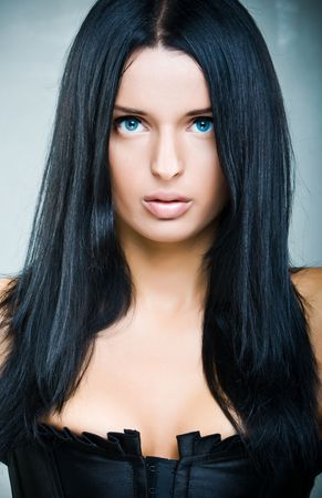 Portrait of beautiful woman with long black hair in fashion style
