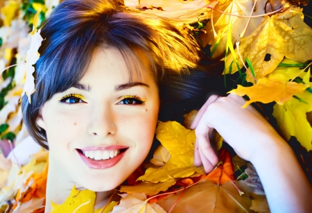 Beautiful smiling young woman in autumn leaves