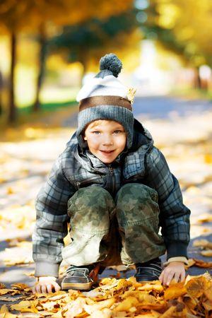 Beautiful little boy play on autumn park photo