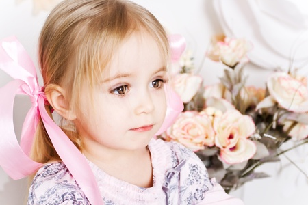 Closeup portrait of beautiful little girl with flowers