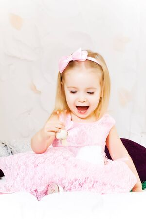Beautiful happy little girl play on white bad photo