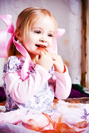 Beautiful little girl play on white bad