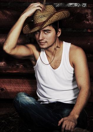 Portrait of brutal cowboy on hayloft Imagens
