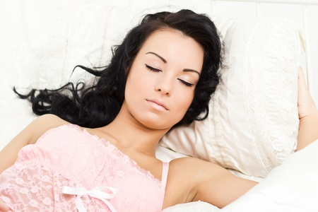 Beautiful young woman sleeping in bright bed
