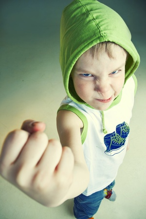 Angry little boy with fist Imagens