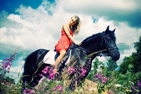 caballo negro: Joven y bella mujer a caballo en el campo de verano