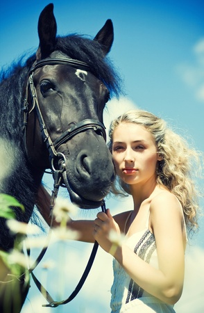 horse blonde: Beautiful young woman with black horse