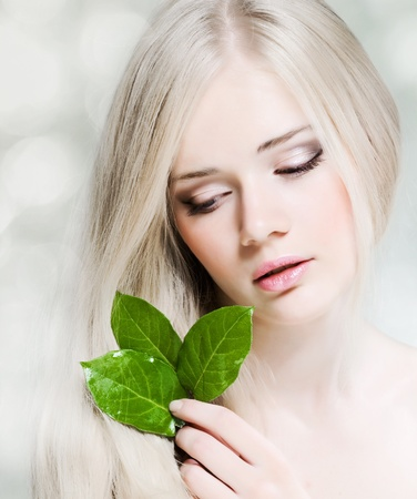 Beautiful young girl with healthy skin and green leaf