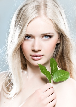 beautiful young girl with healthy skin and green leaf photo