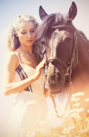 horse blonde: Beautiful woman with black horse at summer morning Stock Photo