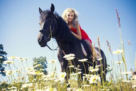 femme et cheval: Belle fille sur cheval noir au terrain de l'été Banque d'images