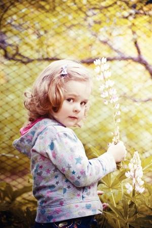 Cute little girl with flower in garden photo