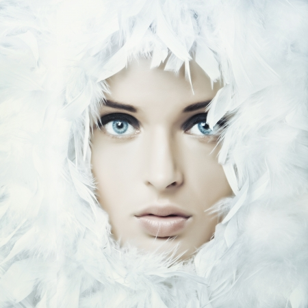 fresh snow: Portrait of beautiful girl in white feathers